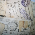 Photograph of assorted historical family postcards, accompanying the FROM HUMBLE ORIGINS' specialised offerings webpage around Possessions showcase the history of your acquisitions, heirlooms and personal business achievements to create a unique record of your family.